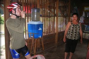Stopping in a village in Laos to drink filtered water from a TerraClear ceramic water filter